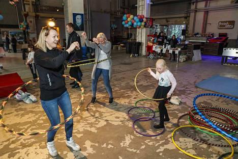 Eveliina Jokinen (vas.) ja Emmi Harjama, innostuivat pyörittämään vanteita kuivaamossa. Mukana Emmi Harjaman tytär Elsa Harjama, 6.
