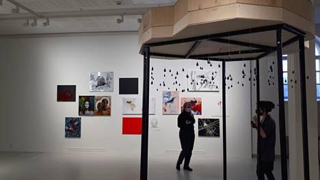 """Etualalla Iina Vartian kineettinen veistos Ikuisen sateen paikka (2021, keramiikka, puu, metalli, sähkömoottorit). Takaseinällä Ulla-Maija Raittilan maalausinstallaatio """"Erityinen äitiys"""" (2021, yhdistelmätekniikka, 14 osaa ja äänitiedosto) Esillä Taidekeskus Mältinrannassa."""