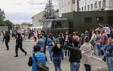 Ihmiset kokontuivat väliaikaisen pidätyskeskuksen edustalle. Pidätettyinä autossa on heidän sukulaisiaan, jotka osallistuivat mielenosoituksiin.