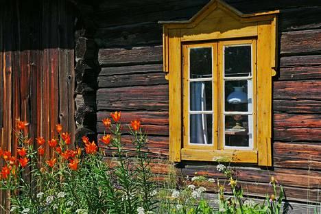 Aurinkoisena kesäpäivänä vanhan hirsirakennuksen ikkuna heijastelee pihapiiriä.