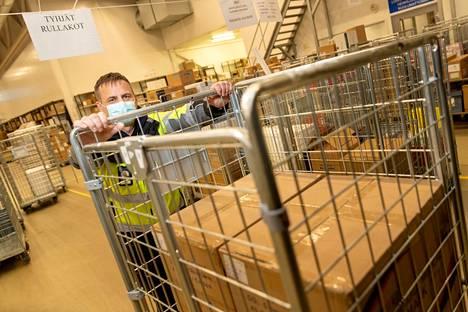 Logistikko Jari Alanissi lastaa rullakot kuoma-autoon. Satasairaalaan menee eniten tavaraa – täysiä kuormallisia ajetaan monta päivässä