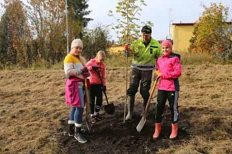Kärjenniemen nejännen luokan oppilaat Vilma Konola, Milla Jokinen ja Ella Väyrynen istuttivat kolme kotipihlajaa Timo Hippeläisen opastusessa.