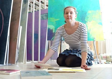 Kati Valkosen puoliso Tomi Valkonen kuvasi Katin työhuoneella. Kuvassa taustalla näkyy telineellä öljyväriteos nimeltä Kartta, joka on tältä vuodelta ja Katin uusin teos.