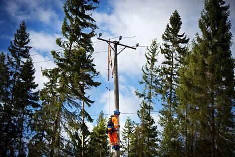 Tuuli aiheutti sähkökatkoja Pirkanmaalla. Sähköyhtiö Elenia urakoitsija Eltel Networksin asentaja Niko Kömi kipuaa tolppakengillä vaihtamaan uutta sähköjohtoa vaurioituneen tilalle Nokian Siurossa