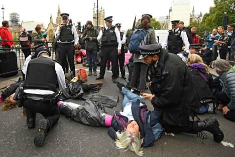 Poliisi pidättää kadun tukkineita mielenosoittajia Lontoossa. Poliisi ilmoitti etukäteen, että kaikki lakia rikkovat mielenosoittajat pidätetään myös rauhanomaisissa protesteissa.