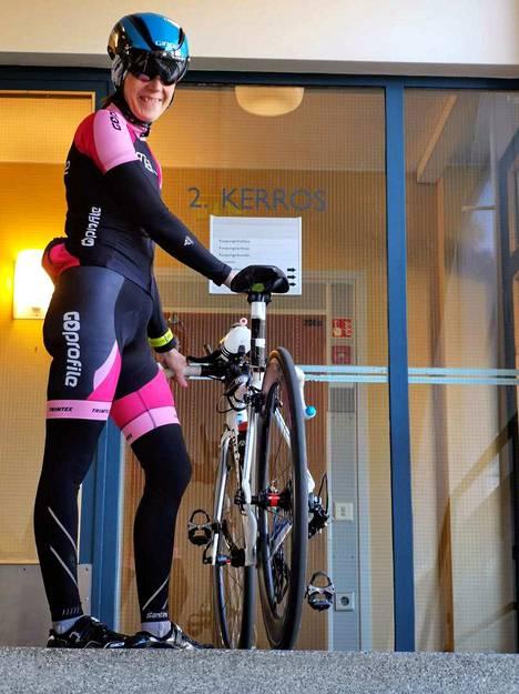 """Anne Laukkanen kantaa työmatkan jälkeen arvokkaan pyöränsä työhuoneeseen. Pyörää on """"tuunattu"""" hänen tarpeisiinsa."""
