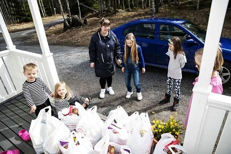 Eveliina Konttinen haki Ylöjärvellä alkaneesta kouluruokajakelusta 84 kiloa ruokaa keskiviikkona. Kotona koululta tuotua ruokakassien määrää ihmettelivät lapset (vasemmalta) Eeti, Liana, Isella, Alviina sekä Elriikka Konttinen.