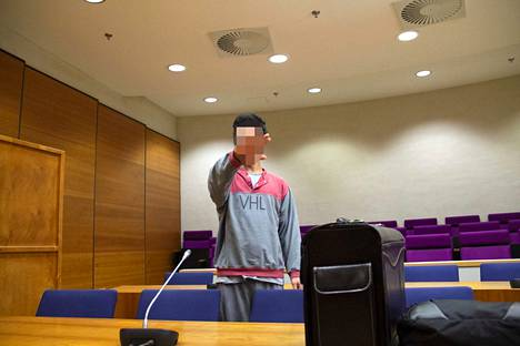 Vuonna 1992 syntynyt vastaaja yritti peittää kasvojaan kädellään oikeudenkäynnin alussa.