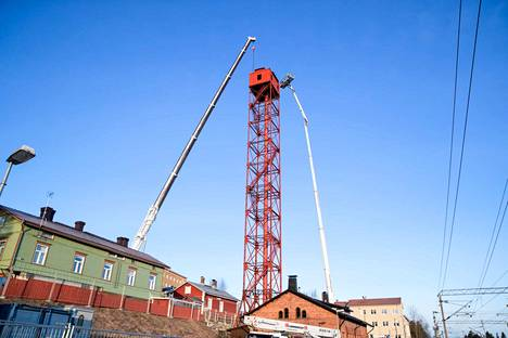 Jouni Alvari ja Tauri Raittoja kohosivat nostolavalla haulitornin huipulle tiistaiaamuna. Nosturi oli valmiina kannattelemaan työhuonetta, jos tornin huippu olisi irrotettu jalustasta.