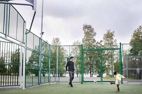 Antti Kangasniemi potki torstaina palloa poikansa Veikon kanssa Lorisevanpuiston peliareenalla. Taustalla näkyy Pyhäjärvi.