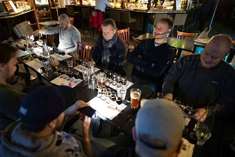 Tunnelma on rento, mutta keskittynyt, kun tusina olutseuralaista tutkii viittä olutta perin pohjin.