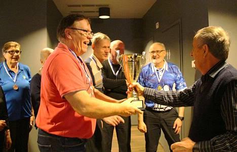 Keuruun miehet ottavat vastaan voittopokaalin joukkuekeilailussa menestymisen kunniaksi. Etualalla Teuvo Perämäki punaisessa paidassa.