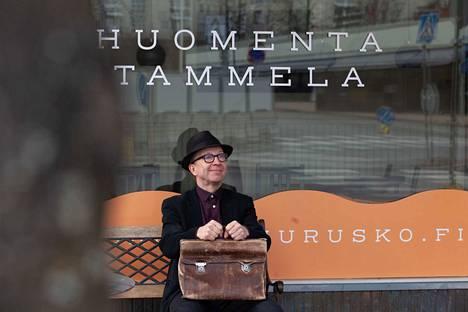 """Tämän valokuvan nimi on """"Huomenta Tammela"""". Simo Frangénin tapa on käydä paljon ulkona niin kahviloissa kuin pubeissa. Tässä hän istuu yhden suosikkikahvilansa Aamuruskon edessä. Kuvassa voi nähdä odotuksen tunnelman, sillä Simo – kuten moni muukin - odottaa kivan kahvila- ja ravintolaelämän käynnistymistä."""