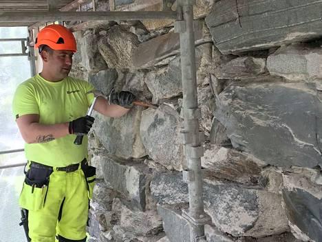 Andrey Paraskevov raaputtaa vanhaa rappausta irti kirkon seinästä. Hän veikkaa, että uusi rappaus tulee kestämään ainakin 30 vuotta