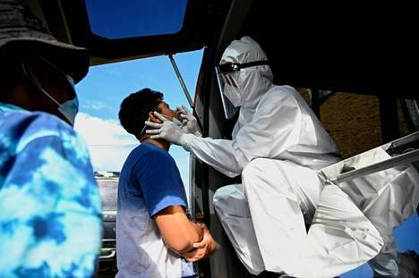 Terveydenhuollon työntekijä tekee koronatestiä Lambarossa, Acehin provinssissa Indonesiassa.