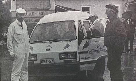 Valkoisiin pukeutunut sähköteknikko Janne Alin esitteli valkoista sähköautoa Korkeakoskella. Lauri Merioksa (oik.) kuunteli kiinnostuneena. Hämeen Sähkön Elcat-sähköautolla pääsi yhdellä latauksella 60-120 kilometriä.