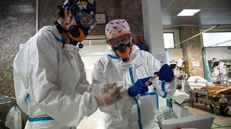 Italialainen sairaanhoitaja ja lääkäri hoitamassa koronapotilaita marraskuun lopussa Genovan kaupungissa.