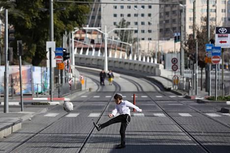 Lapsi pelasi jalkapalloa keskellä katua Jerusalemissa vuoden alussa, kun Israeliin oli määrätty voimakkaita koronavirusrajoituksia.