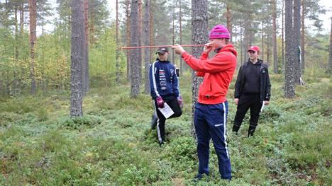 Oula Kyösti, Jere Kerola ja Leo Myllymäki mittaavat ympäröivän alueen puuston tilavuutta.