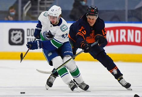 Jesse Puljujärvi (takana) yritti pysäyttää Vancouverin Quinn Hughesia.