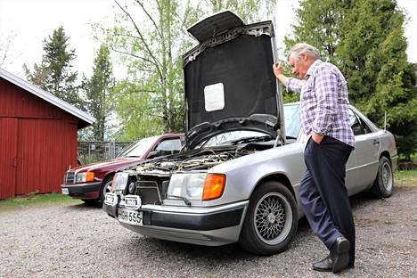 """Mercedesin konepelti avautuu niin, että moottoriin varmasti pääsee käsiksi, Tapani Räsänen näyttää. Takaa pilkottaa miehen järjestyksessä kahdeksas """"Johtotähti"""", Mercedes-Benz 190E vuodelta 1989, joka on jo museorekisterissä."""