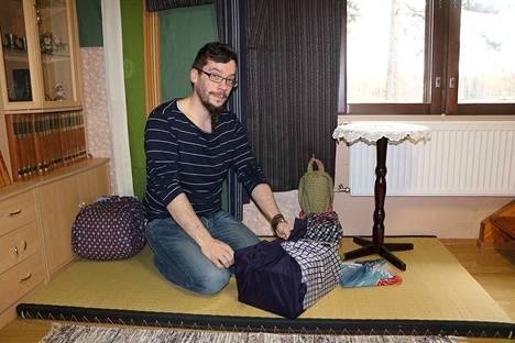 Ari-Pekka Heikkilä istuu tyypillisessä japanilaisessa asennossa tatamilla. Pakkaukset on kääräisty furoshiki-liinoihin. Taustalla on kimono, joka on yleisnimitys japanilaiselle asusteelle.