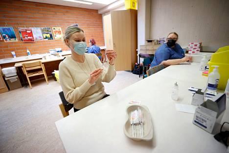Suurimmassa osassa Satakuntaa rokotusvuorossa ovat nyt jo 50-vuotiaat. Arkistokuvassa terveydenhoitajat Annikka Lehtisalo-Pohjola (vas) ja Titta Valkama laimentavat rokotteita Porin nuorisotalolla.