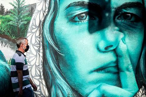Hengityssuojaimeen pukeutunut mies käveli torstaina muraalin editse Brasilian Sao Paulossa, joka on maan koronaviruskeskittymä. Brasiliassa on kolmanneksi eniten tartuntoja maailmassa.