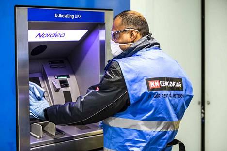 Työntekijä puhdisti ja desinfioi metroaseman nostoautomaattia Kööpenhaminassa tiistaina.