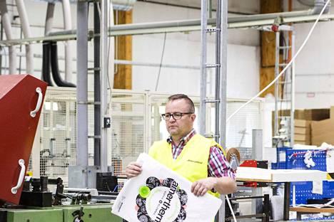 """Tuotantopäällikkö Sami Teräs käsissään esimerkiksi pakastetuotteiden kuljettamiseen suunniteltu termokassi. """"Termokassissa kierrätysmateriaalien osuus on yli 50 prosenttia"""", Teräs kertoo."""