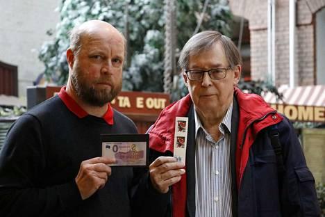 Näyttelypäällikkö Jukka Kaivanto (vas.) ja seuran pitkäaikainen puheenjohtaja Kari Salonen esittelevät juhlanäyttelyn yksiä harvinaisuuksia. Barkov-postimerkkiä ja 0 euron seteliä.