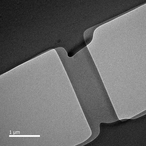Plastisen lasin venytys- ja puristuskokeet tehtiin Ranskassa Lyonissa läpivalaisuelektronimikroskoopilla. Kuvan keskellä näkyvä kaistale on venyvää lasimaista alumiinioksidia. Muodonmuutosta läpivalaistiin reaaliajassa elektroneilla. Näin saatiin todisteita ilmiön aiheuttavista mekanismeista. Kuvassa näkyvän alueen leveys on noin viisi mikrometriä eli millimetrin tuhannesosaa.