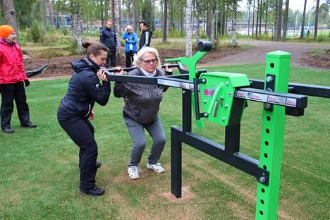 Heidi Harju opasti Pirjo Enonkoskea kuntoilulaitteen käytössä.
