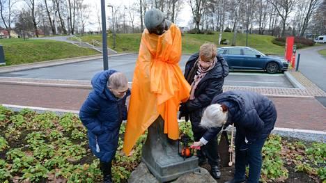 Marjatta-veistos sai oranssia ylleen Valkeakosken keskustassa tiistaina. Lisäksi kuvan Marjatta Ventonen, Marjatta Sievers ja Marketta Sarvikas sytyttivät kynttilän veistokselle.