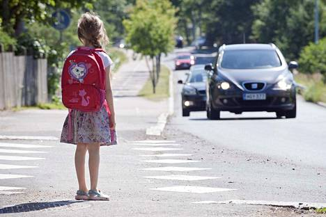 Normaalikoulun edustalla Kuokkamaantiellä vapaaehtoiset suojatiepäivystäjät herättävät autoilijoiden huomiota ja auttavat pienempiä koululaisia turvallisesti kadun yli.