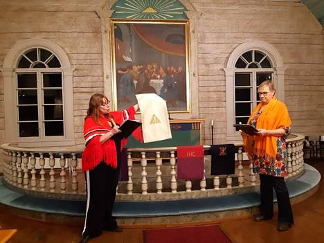 Väreistä voimaa -tilaisuuden ohjaaja Päivi Honkala esittelee valkoista lukupulpettiliinan väriä runoilija Päivi Äikäälle. Kaikki viisi liturgista väriä esitellään ja kerrotaan, mitä väreillä viestitetään eri kirkkopyhinä.