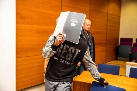 Mies peitti kasvonsa Pirkanmaan käräjäoikeudessa vangitsemisistunnossa vuoden 2020 maaliskuussa.