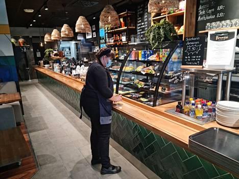 Uusittu Siilinkarin kahvilaa hallitsee nyt pitkä tuotetiski. Minna Kuurila on täyttämässä vitriiniä.
