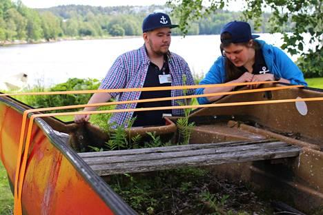 Satamatoimiston kesätyöntekijät Viljo Palonen ja Jenny Kovanen hankkivat maatuneelle veneelle kuljetuksen pois rannasta.