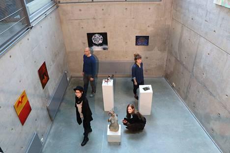 Opiskelijoiden iso syysnäyttely levittäytyy myös taidekoulun alakertaan. Teosten keskellä Leo Pulkkinen ja Annika Takkala (edessä) sekä Into Kaataja ja Iina Vartia (takana).