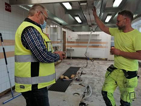 Ari Suoranta ja Marko Padatsu keskustelevat Savosenmäen koulun keittiön kunnostustöiden etenemisestä. Uusi lattiapinta valmistunee heinäkuun alkupuolella.