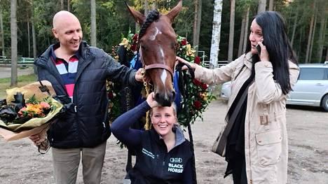 Kriterium-voittaja Sahara Jaeburn on Petra Huhtin kasvatustyön kirkkain tähti. Oriin kanssa poseeraavat hoitaja Tessa Länsimäki, omistaja Petra Huhti (puhelin korvalla vastaanottamassa onnitteluja) ja Huhtin puoliso Oskari Mäenpää.