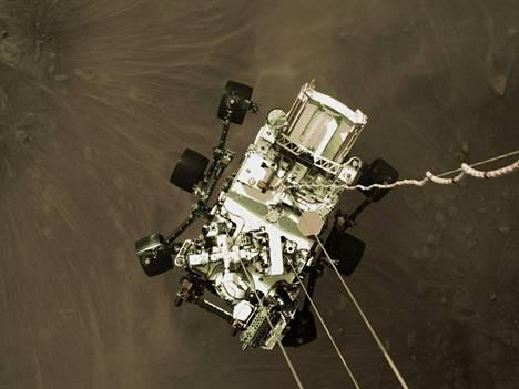 Perseverance-avaruusmönkijä ylhäältä kuvattuna. Mönkijä laskettiin Marsin pinnalle kaapeleilla.
