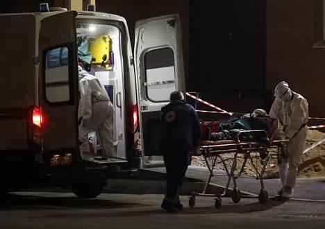 Suojavarusteita käyttävät ensihoitajat toivat potilasta sairaalaan joulukuun alussa Pietarissa Venäjällä.