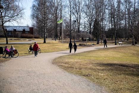 Ulkoilijat ottivat ilon irti lämpimästä ja aurinkoisesta säästä Hatanpään Arboretumilla. Keväisistä säistä huolimatta nurmikko ei vielä viherrä.
