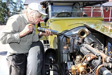 Sata vuotta sitten autonkuljettajat pitivät herrain autot kunnossa, mutta Pertti Nikkilä osaa tehdä kaiken tarvittavan itse. Ensimmäisenä puristetaan öljyä kardaaniakselille ja -nivelelle.