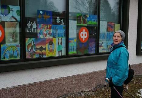 Ritva Läpinen ihastelee Kolhon oppilaiden kilpailutöitä, jotka on ripustettu pankin Kolhon konttorin ikkunaan.