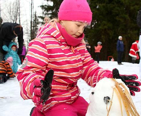 Koko kylän jouluriehassa Mäntän Vuorenmajalla Jenisha Rättö, 7, teki lumiakan.