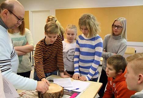 Juupajoen koulukeskuksen ja Kopsamon koulun kuudesluokkalaiset laskevat männyn ikää vuosirenkaista Masu-projektin Maalta ja Metsästä -teemapäivässä.