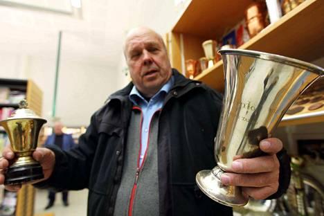 Pentti Koskinen pitelee käsissään näyttelyn vanhimpia palkintoja. Pienempi pokaali on kiertopalkinto vuodelta 1950 Kuoreveden Kärjen ja Toverien uintiottelusta. Isompi pokaali on painin kiertopalkinto vuodelta 1954.
